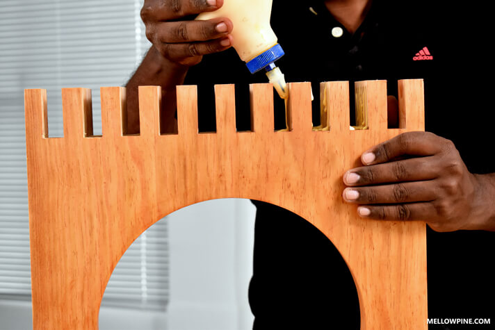 Applying glue in the slots of the legs before fixing the slats inside