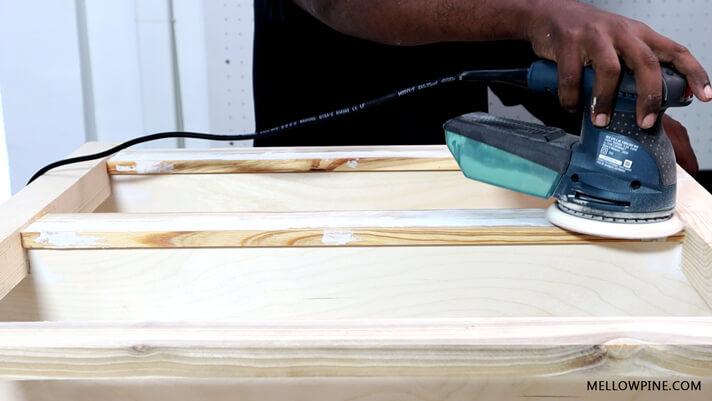 Sanding the wood filler using a sander