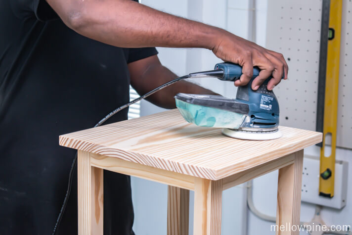 Sanding the top piece of the bar stool