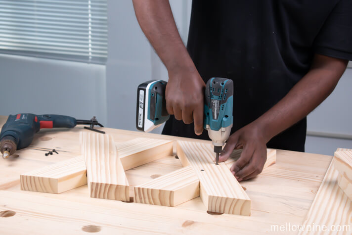 Screwing the X brace pieces together using wood screws